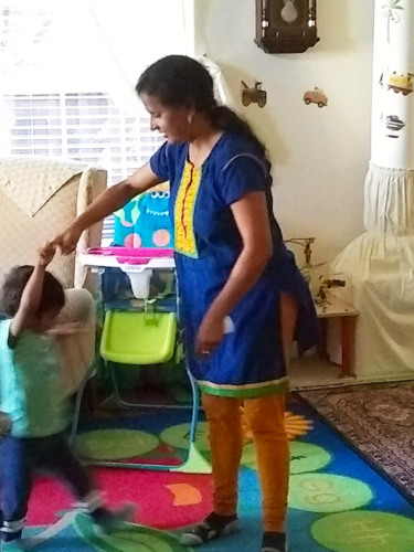 Daycare helper and child dancing to Bollywood music