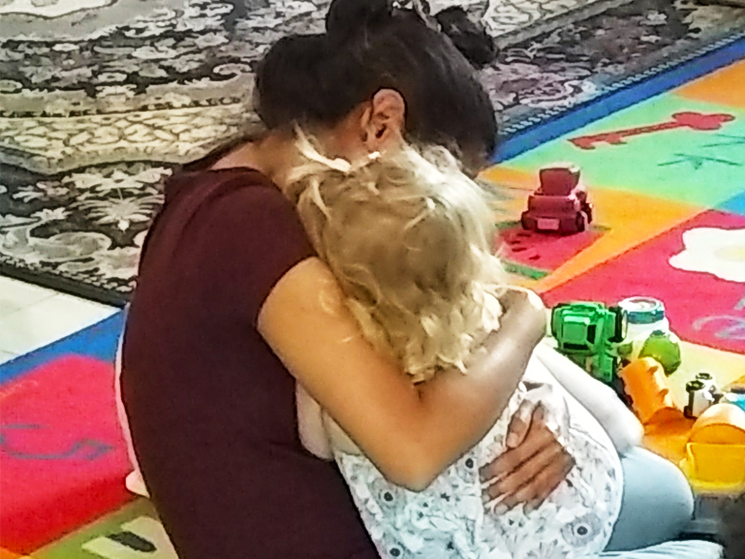 Daycare helper hugging girl while sitting on colorful rug