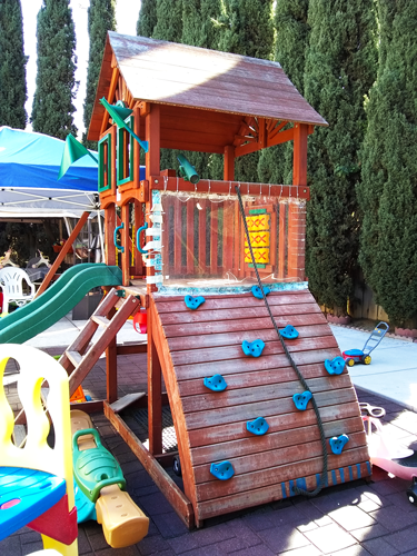 Slide with house enclosure and climbing wall