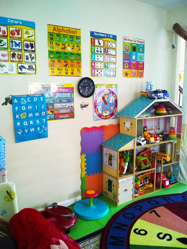 Alphabet, numbers, and colors educational signs with dollhouse and toys in daycare play area