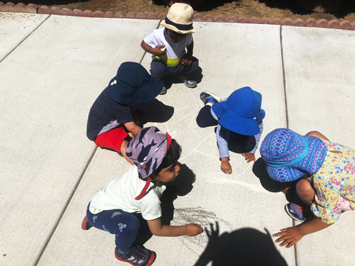 Children drawing on sidewalk with chalk