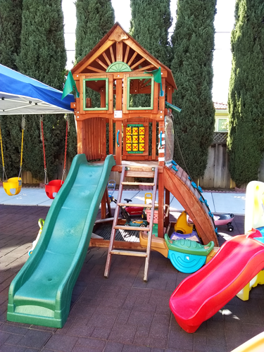 Large wood play set with slide in outside play area