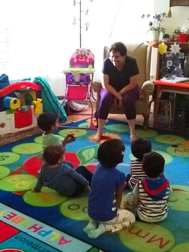 Children sitting on colorful rug engaging with preschool director