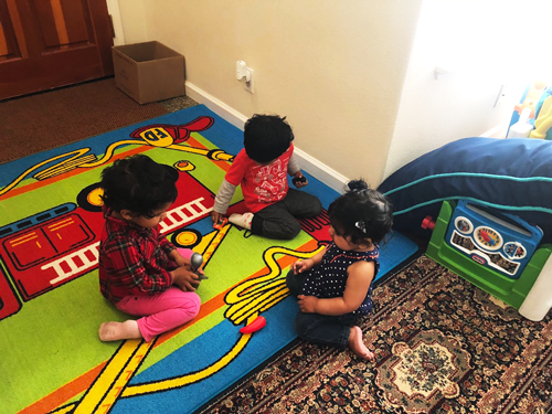 Three children playing on colorful rug