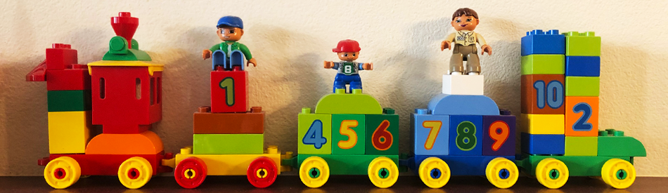 Children's toy lego train with toy people riding on it