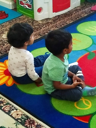 Two children sitting on colorful rug